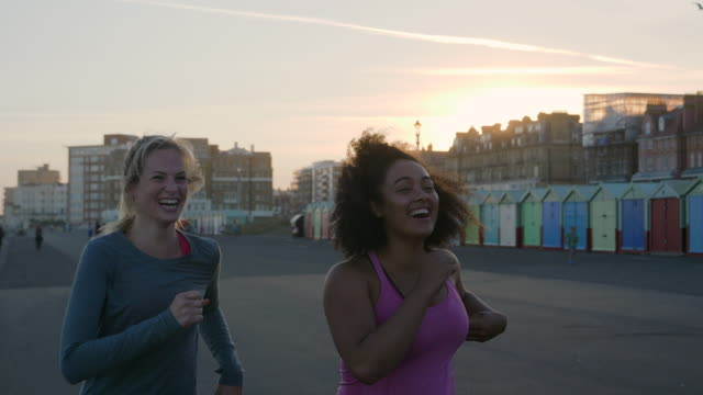 two women running down the promenade at sunset. - friendship stock videos & royalty-free footage