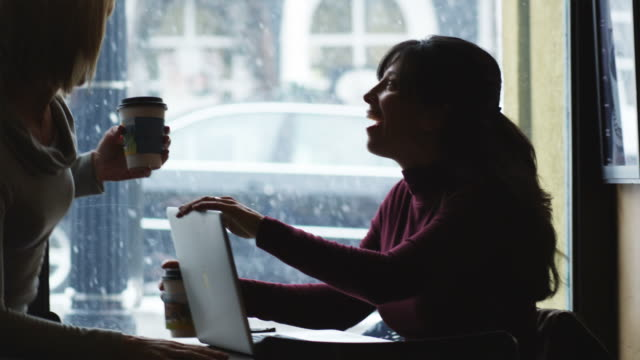 two women running into each other at a coffee shop
