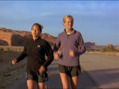 two women running on road in the southwest outdoors - 女性ランナー点の映像素材/bロール
