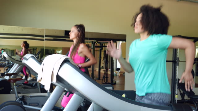 two women running on treadmills in gym - treadmill stock videos & royalty-free footage