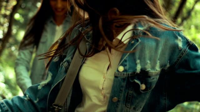 vídeos de stock, filmes e b-roll de duas mulheres correndo pela floresta - jaqueta jeans