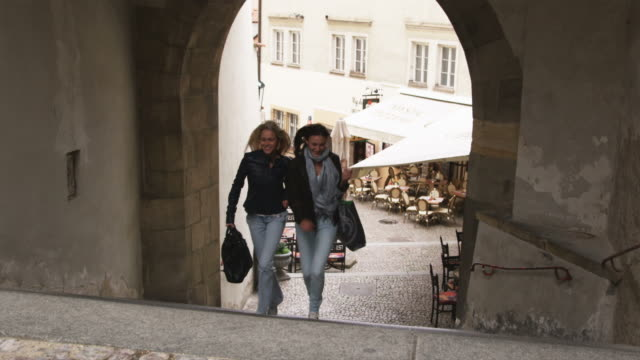 two women running up the stairs on a city street - prague stock videos & royalty-free footage