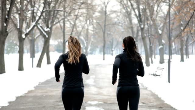 vídeos de stock, filmes e b-roll de duas mulheres correndo - calça comprida