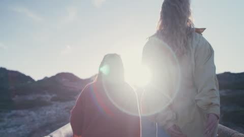 vídeos y material grabado en eventos de stock de two women running/walking in hills by beach - amigos
