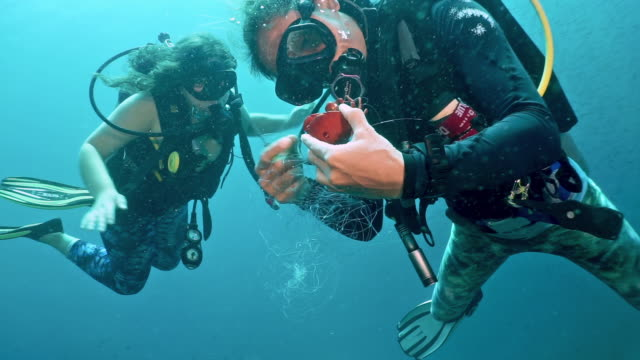 two women scuba divers rescue trapped crab from discarded fishing ghost net underwater - a helping hand stock videos & royalty-free footage
