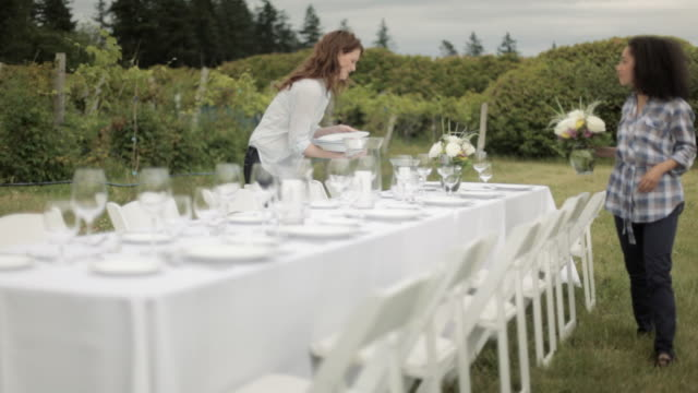Two women setting table for dinner party in a field