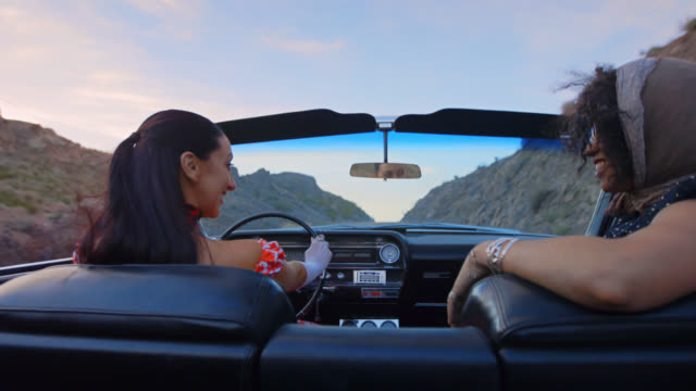 ms. two women share a laugh on a desert drive in a classic convertible. - formal glove stock videos & royalty-free footage