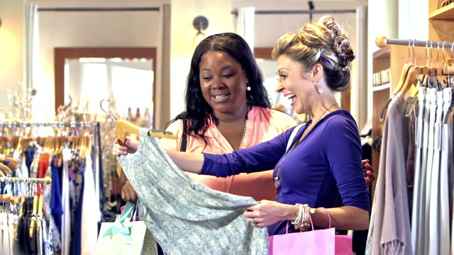 Two women shopping for clothing, in store talking