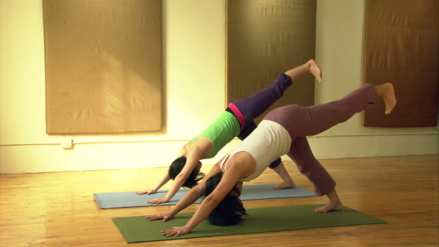 ws two women side by side on mats in yoga studio, bending over and lifting legs in air/ new york, ny - side by side stock videos & royalty-free footage