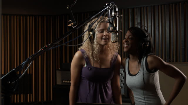 two women singing in a recording studio