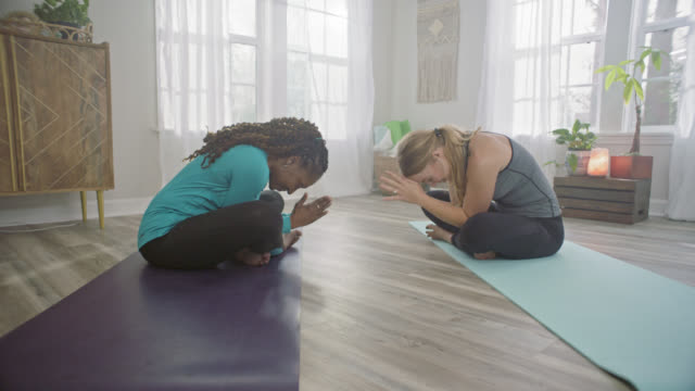 SLO MO. Two women sit across from each other on yoga mats and bow with hands in prayer position.