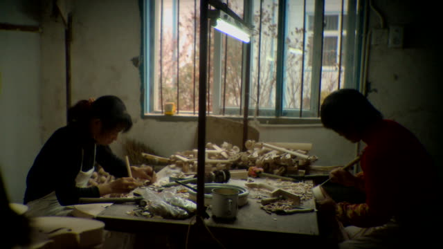 vídeos y material grabado en eventos de stock de ms two women sitting at messy tabletop making violins in factory, taizhou-taixing factory, taizhou, jiangsu, china - herramienta de mano