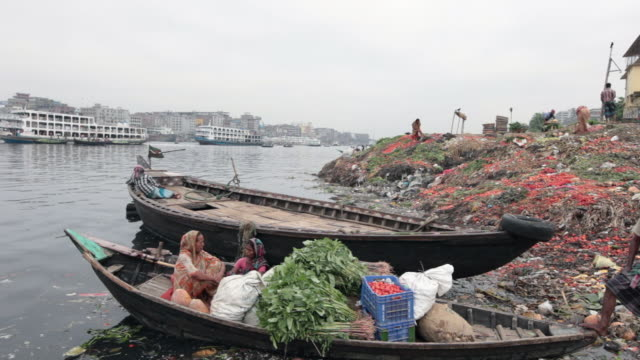 vidéos et rushes de two women sitting in a boat full of vegetables in front of an enormous garbage disposal on buriganga river bank, not far from the sadarghat boat terminal, dhaka, bangladesh, indian sub-continent, asia - bangladesh
