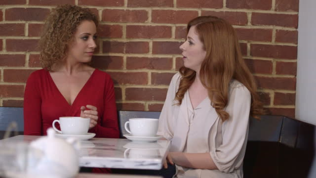 two women sitting in cafã© - greater london video stock e b–roll