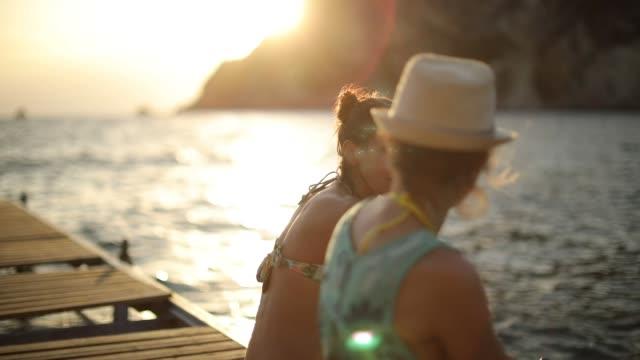 vídeos de stock e filmes b-roll de two women sitting on a pier at sunset - pier