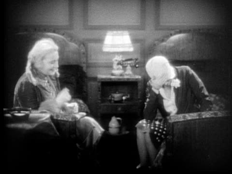 ms, b&w, two women sitting on beds in hotel room, 1920's  - anno 1928 video stock e b–roll