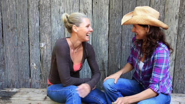 MS Two women sitting on bench and talking and laughing / Idaho, United States