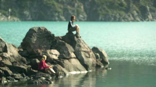 ms two women sitting on big boulder by water's edge, garibaldi provincial park, squamish, british columbia, canada - garibaldi park stock videos & royalty-free footage