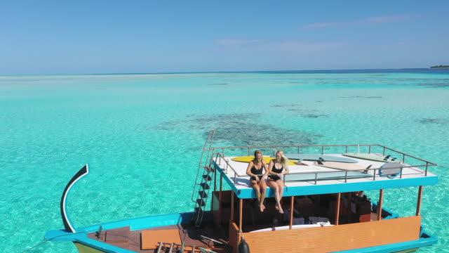 stockvideo's en b-roll-footage met twee vrouwen die op boot met het surfen planken zitten en van oceaan genieten - peddel