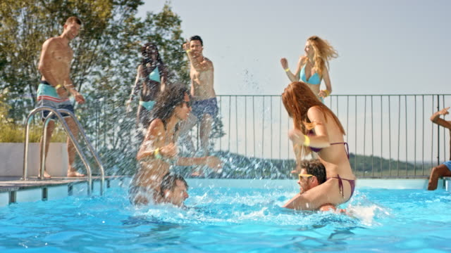 SLO MO DS Two women sitting on men's shoulders in the pool and splashing each other