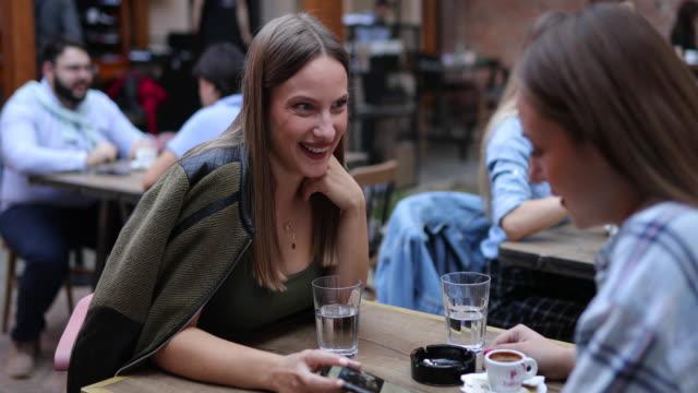 vídeos y material grabado en eventos de stock de dos mujeres sentadas al aire libre en el café - pub