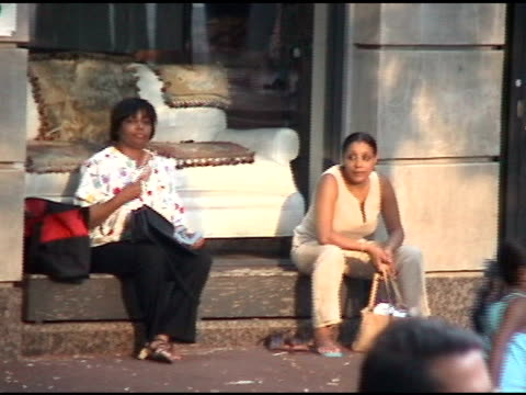 Two women sitting waiting in front of shop window during the 2003 blackout in Manhattan 2003 blackout two women waiting on August 14 2003 in New York...