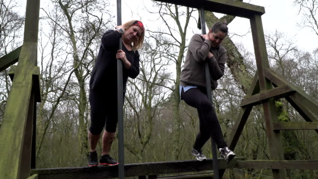 Two Women sliding down pole on Assault Course / Obstacle course - Slow Motion