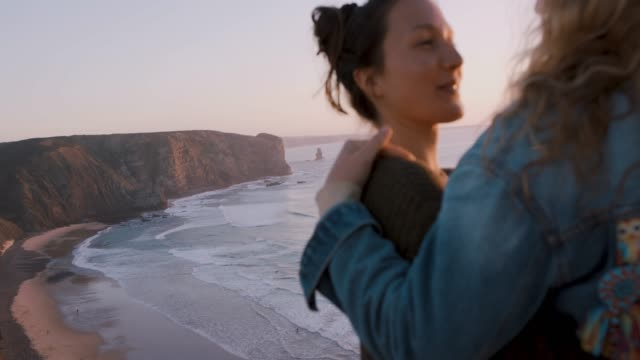 Two women smiling, talking, laughing on sea cliff at sunset