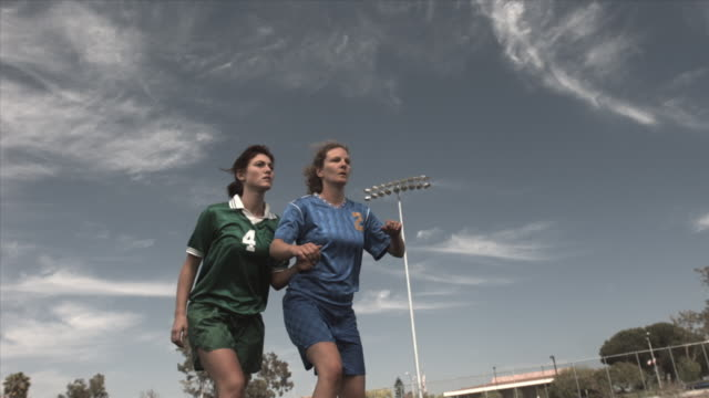 vidéos et rushes de slo mo la ms two women soccer players jumping up to head soccer ball on field at biola university / la mirada, california, usa - joueur de football
