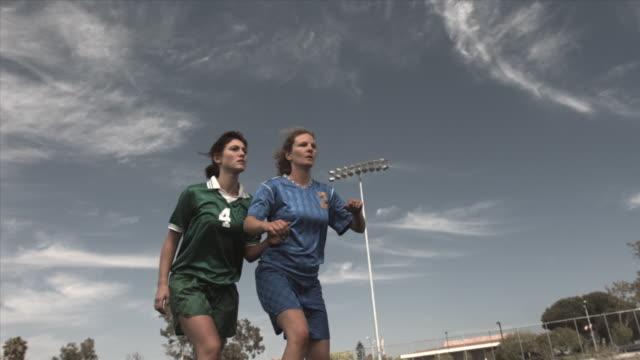 vídeos de stock, filmes e b-roll de slo mo la ms two women soccer players jumping up to head soccer ball on field at biola university / la mirada, california, usa - sexo feminino