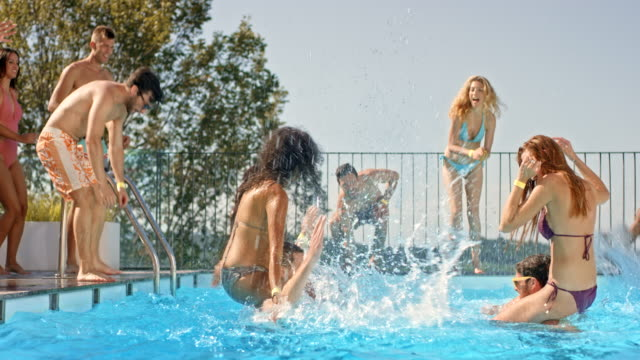 DS Two women splashing each other in the pool while sitting on men's shoulders