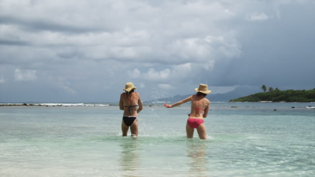 two women splashing in the ocean - tahaa island stock videos & royalty-free footage