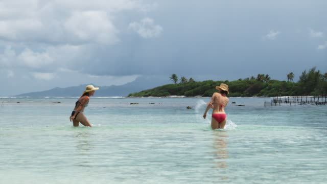 two women splashing in the ocean - isola di tahaa video stock e b–roll