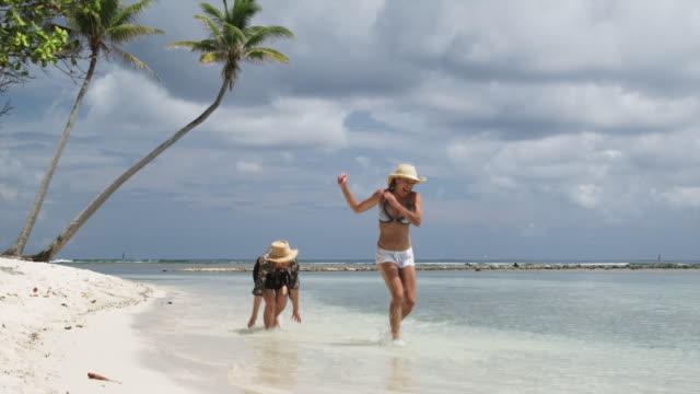 two women splashing on the beach - tahaa island stock videos & royalty-free footage
