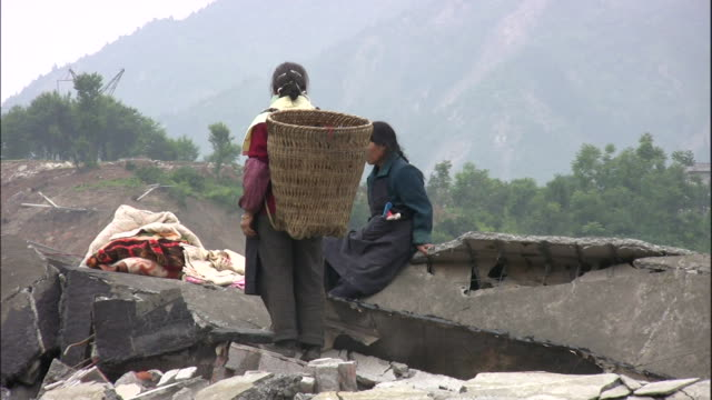 two women stand on rubble after the 2008 earthquake in sichuan china - survival stock videos & royalty-free footage