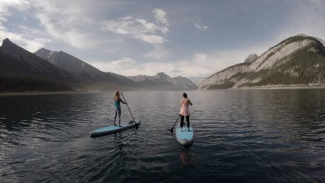 Zwei Frauen stand up Paddle boarding auf Alpensee