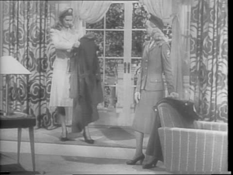 vídeos y material grabado en eventos de stock de two women standing in a living room like setting in front of a window, modeling nurse rain coats, berets, cotton summer separates / women demonstrate... - sobretodo