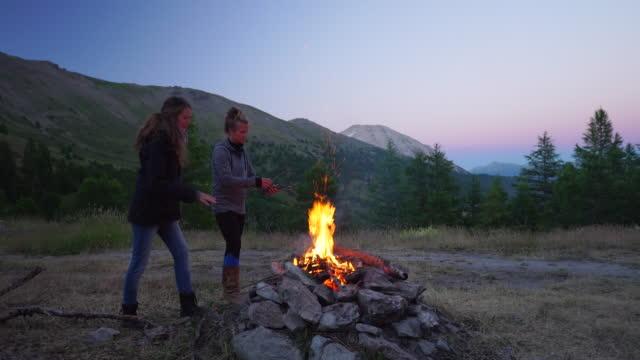 Two women stoke campfire
