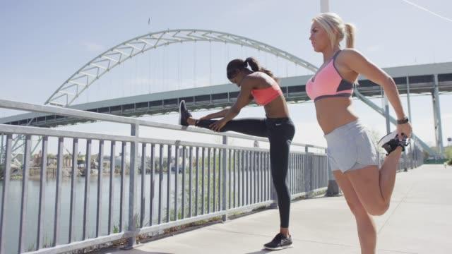 vídeos de stock, filmes e b-roll de duas mulheres de alongamento antes de uma corrida - sutiã para esportes