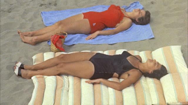 MS Two women sunbathing on beach, Viareggio's sandy beach, Tuscany, Italy.