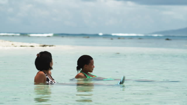 two women swimming in the ocean - tahaa island stock videos & royalty-free footage