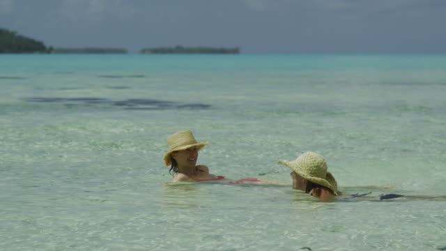 two women swimming in the ocean - isola di tahaa video stock e b–roll
