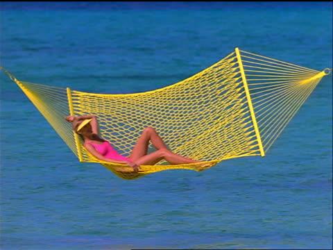 pan two women swinging in large brightly colored hammocks / ocean in background / bahamas - ワンピース型の水着点の映像素材/bロール