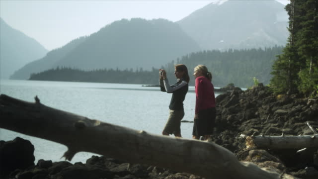 ms r/f pan two women taking photographs standing by lake's edge, garibaldi provincial park, squamish, british columbia, canada - garibaldi park stock videos & royalty-free footage