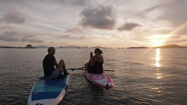 stockvideo's en b-roll-footage met twee vrouwen die foto's op mobiele telefoon paddleboarding bij overzees nemen - peddel