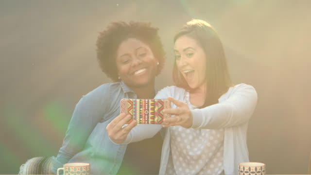 two women taking selfie together with smartphone - amicizia tra donne video stock e b–roll