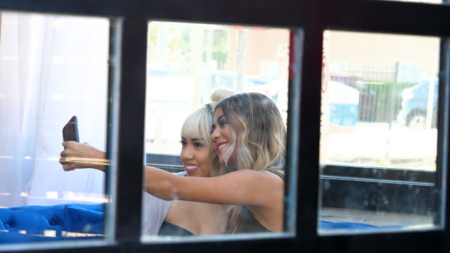 MS Two women taking selfie together with smartphone while sitting in bar