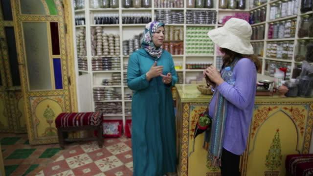 two women talk in store - naher und mittlerer osten stock-videos und b-roll-filmmaterial