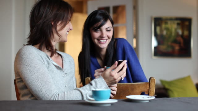 MS Two women talking and showing photos on mobile phone sitting at dining table / Brussels, Brabant, Belgium