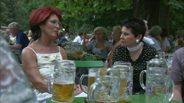 stockvideo's en b-roll-footage met ms two women talking at beer garden, beer glasses in foreground, englischer garten (english garden), munich, bavaria, germany - stippen